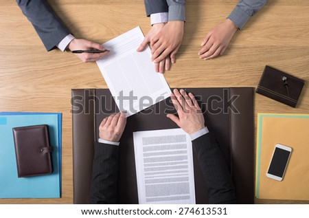 Couple sitting at the notary's desk and signing marriage documents, hands top view, unrecognizable people - stock photo
