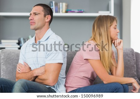Couple sitting back to back after a fight on the couch in sitting room at home - stock photo