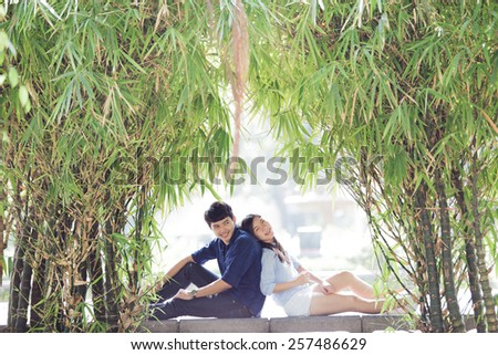 Couple sitting back to back and smile happiness. Them are in garden. - stock photo