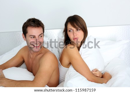 Couple sitting back to back in bed, arguing - stock photo