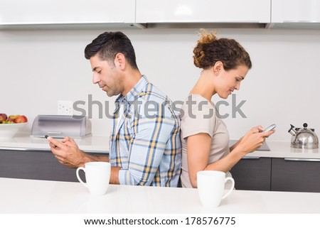 Couple sitting back to back texting at home in kitchen - stock photo