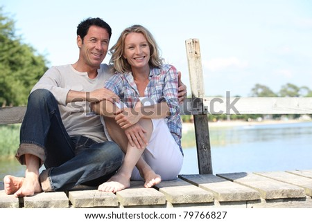 Couple sitting by a lake - stock photo
