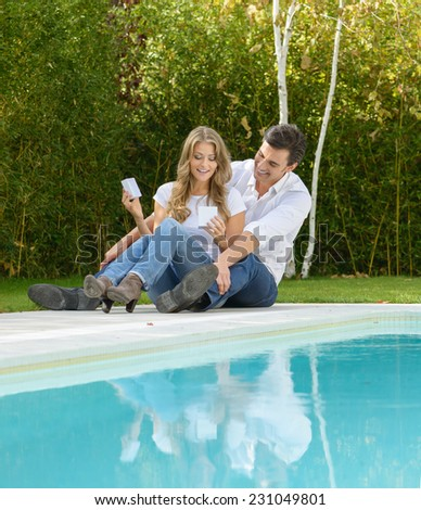 Couple sitting by the pool with the girl opening a gift box - stock photo
