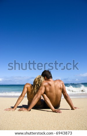 Couple sitting close together on Maui, Hawaii beach looking out at ocean. - stock photo