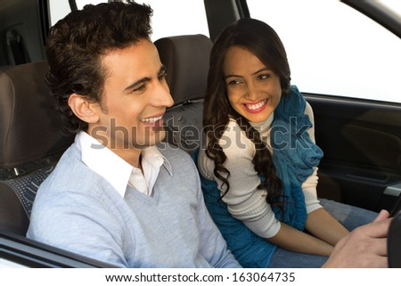 Couple sitting in a car and smiling