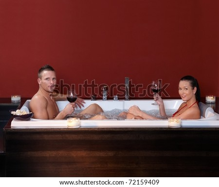 Couple sitting in bubble bath, having red wine in wellness environment, looking at camera.? - stock photo