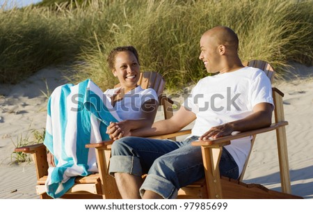 Couple sitting in chairs on beach - stock photo