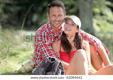 Couple sitting in forest on hiking day - stock photo