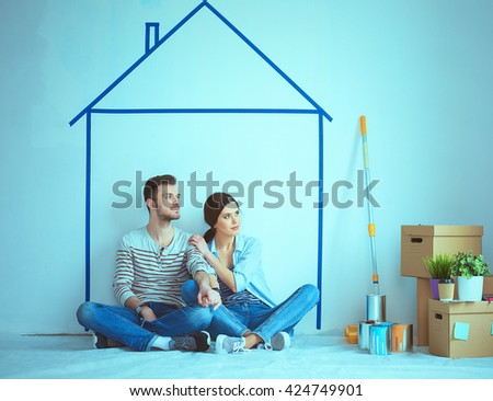 Couple sitting in front of painted home on wall - stock photo