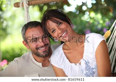 Couple sitting in hammock - stock photo