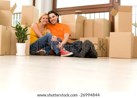 Couple sitting in new home - stock photo