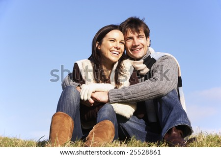 Couple Sitting In Park Together - stock photo