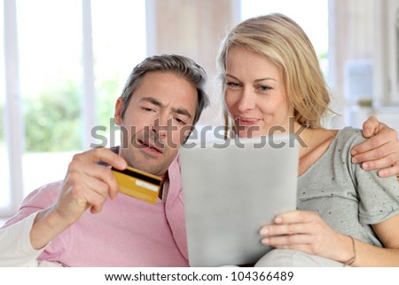 Couple sitting in sofa at home and doing online shopping - stock photo
