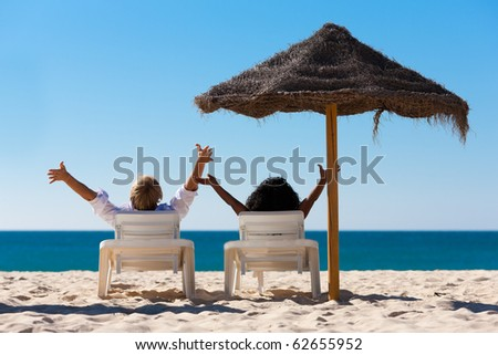 Couple sitting in sun chairs under an parasol sunshade on a beach stretching arms, feeling free