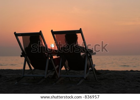 Couple sitting in the chairs watching sunset at the beach - stock photo