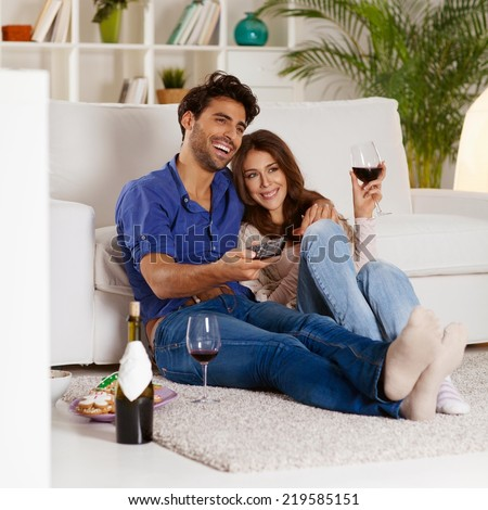 Couple sitting in the living room, having wine and watching TV. - stock photo