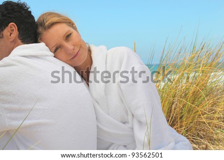 Couple sitting in the sand dunes in white toweling robes