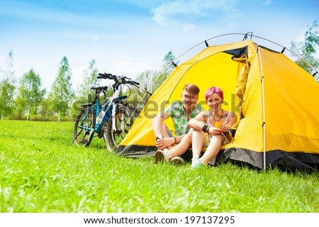 Couple sitting in the tent and drinking tea with bikes standing near - stock photo