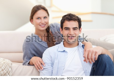 Couple sitting in their living room while looking at the camera - stock photo