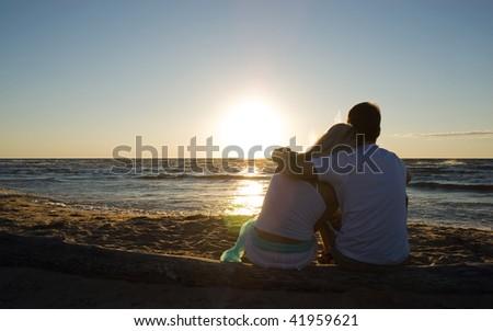 Couple sitting near the sea on sunset - stock photo