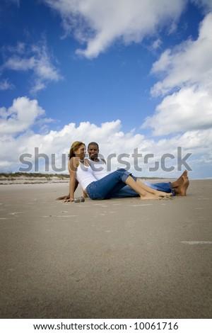 Couple sitting on a beach - stock photo