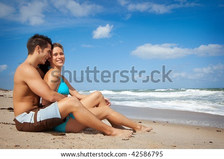 Couple sitting on a beach, both smiling, happy