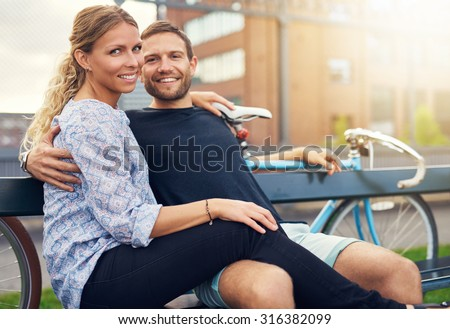 Couple sitting on a bench looking into the camera - stock photo