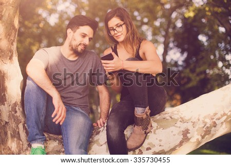 Couple sitting on a branch and looking at mobile phone - stock photo