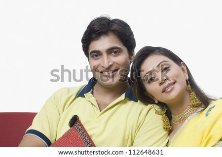 Couple sitting on a couch and smiling - stock photo