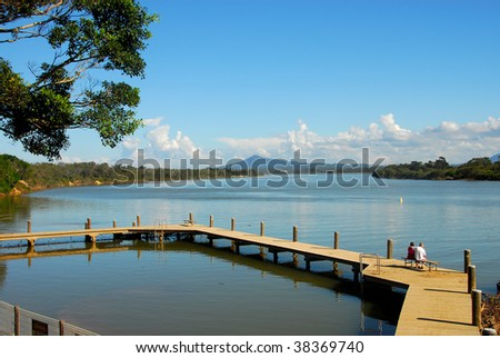 Couple Sitting on a Dock By the River Enjoying the View