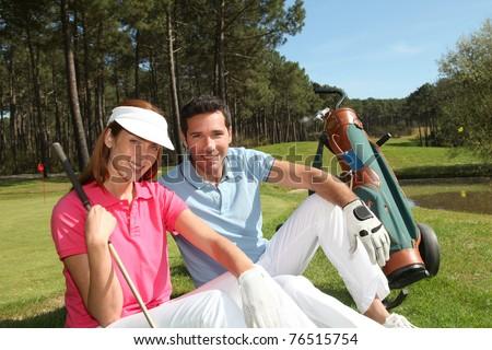 Couple sitting on a golfcourse - stock photo