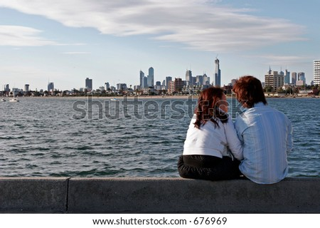 Couple sitting on a pier looking at the Melbourne Skyline - stock photo