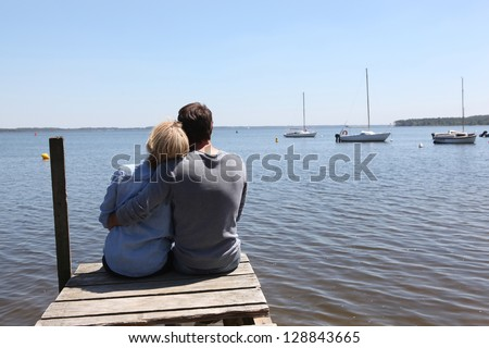 Couple sitting on a pontoon - stock photo