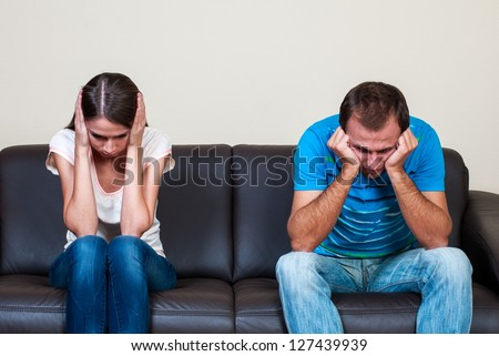Couple sitting on a sofa mad at each other - stock photo