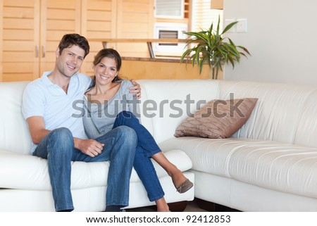 Couple sitting on a sofa while looking at the camera - stock photo