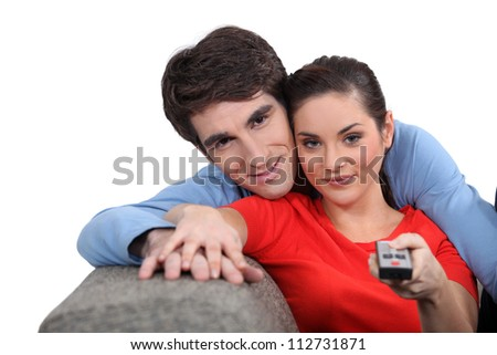Couple sitting on a sofa with a remote control - stock photo