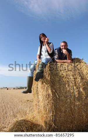 Couple sitting on bail of hay - stock photo