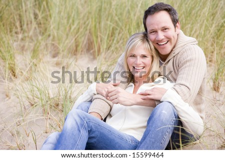 Couple sitting on beach smiling - stock photo
