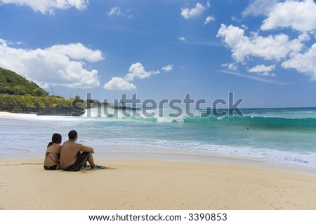 couple sitting on beach watching surfers and sea - stock photo