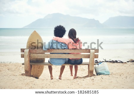 Couple sitting on bench together at the beach in love - stock photo