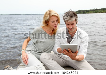 Couple sitting on boardwalk and using tablet - stock photo