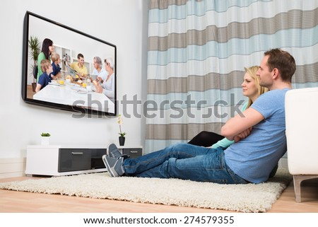 Couple Sitting On Carpet Watching Television In Living Room - stock photo