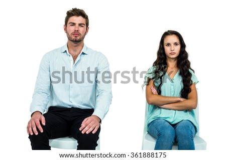 Couple sitting on chairs not talking after argument over white background - stock photo