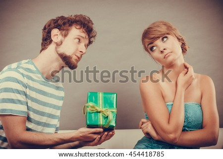 Couple sitting on couch at home. Young man giving offended woman gift box, girl refusing to accept present