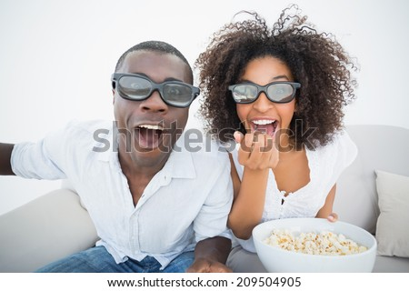 Couple sitting on couch together watching 3d movie at home in the living room - stock photo
