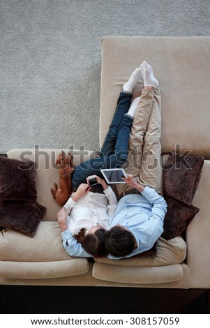 couple sitting on couch with their dog - stock photo