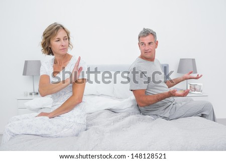 Couple sitting on different sides of bed having an argument in bedroom at home