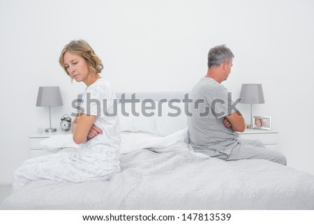 Couple sitting on different sides of bed not talking after fight in bedroom at home - stock photo