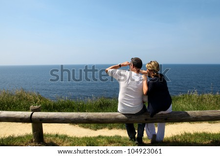 Couple sitting on fence enjoying panoramic sea view - stock photo