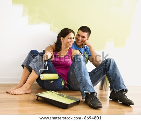 Couple sitting on floor smiling in front of partially painted wall in home. - stock photo
